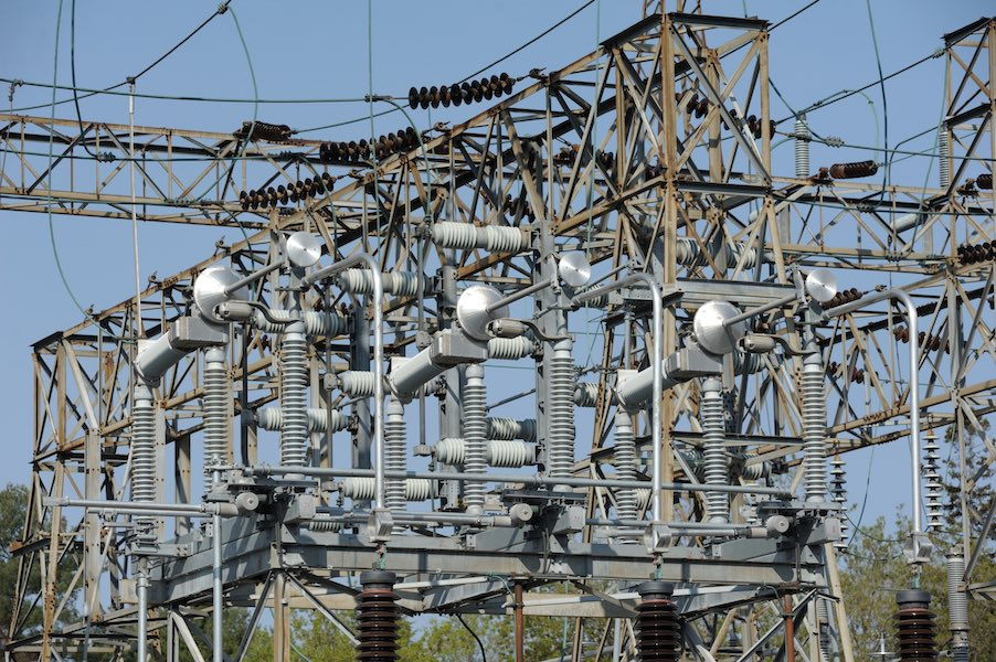An urban electrical power transmission sub-station. Electrical components such as power lines insulators are visible.